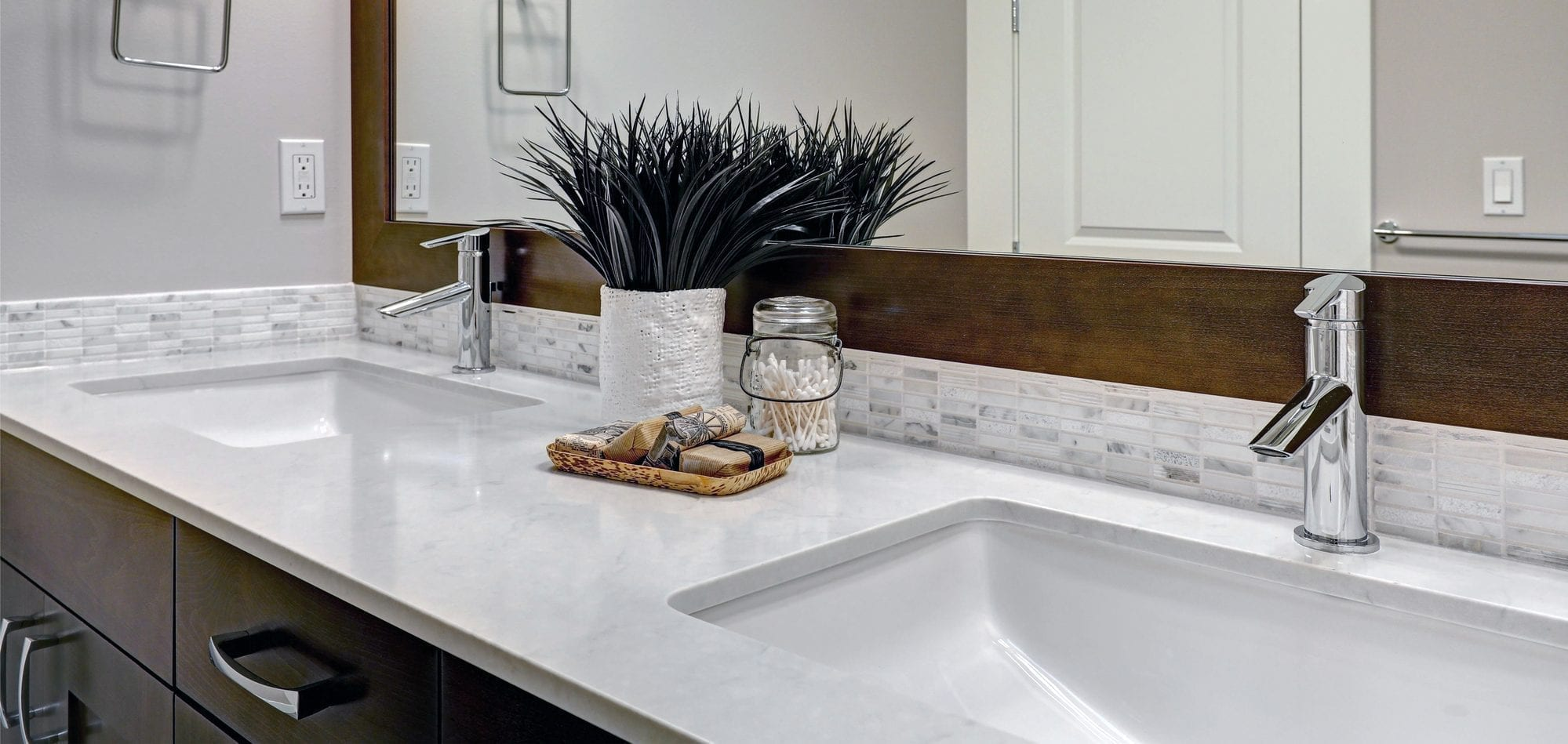 White and brown bathroom boasts a nook filled with double sink bathroom vanity cabinet topped with white and grey counter paired with tile backsplash under framed mirror.