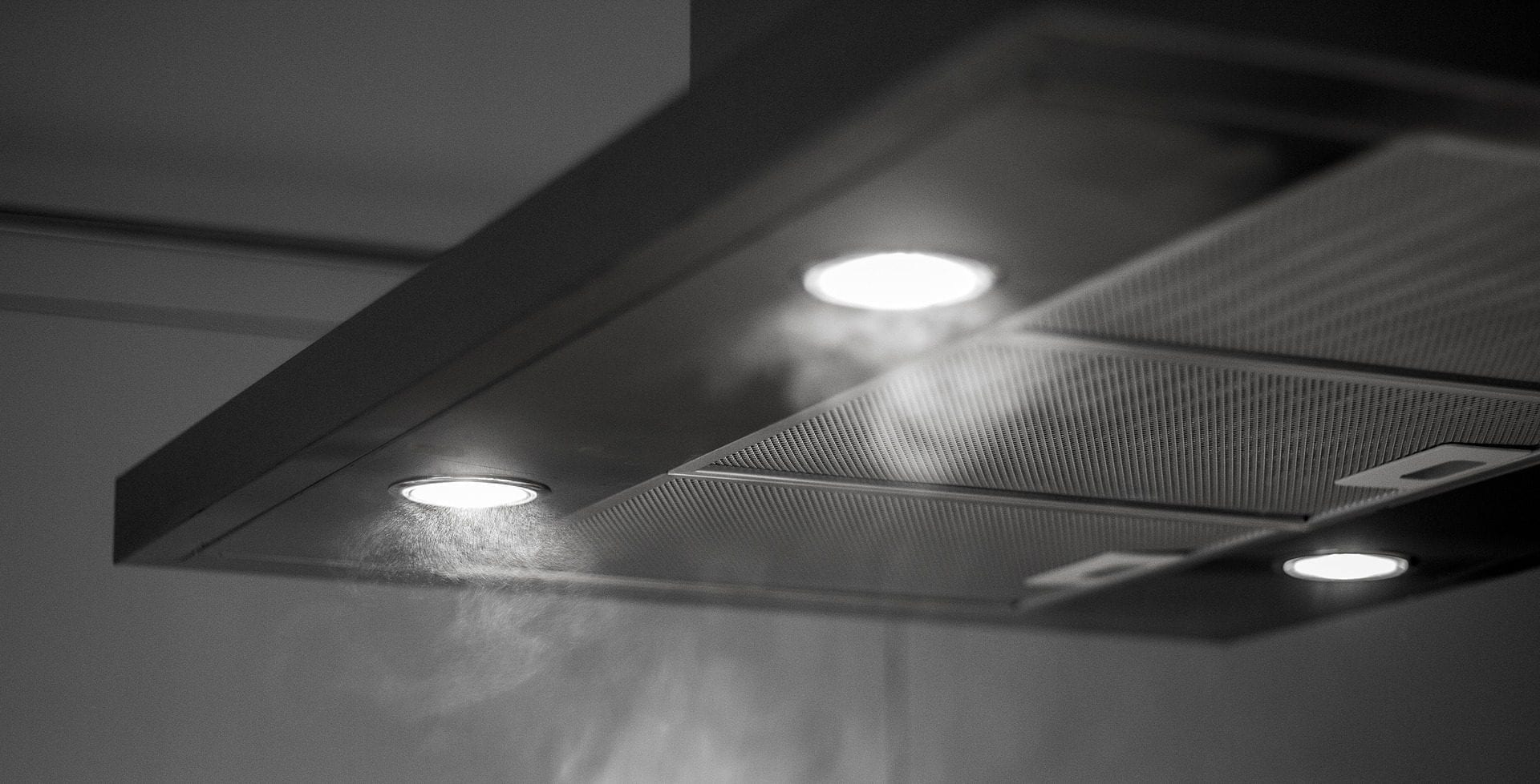 Black and white image of stove lighting in kitchen
