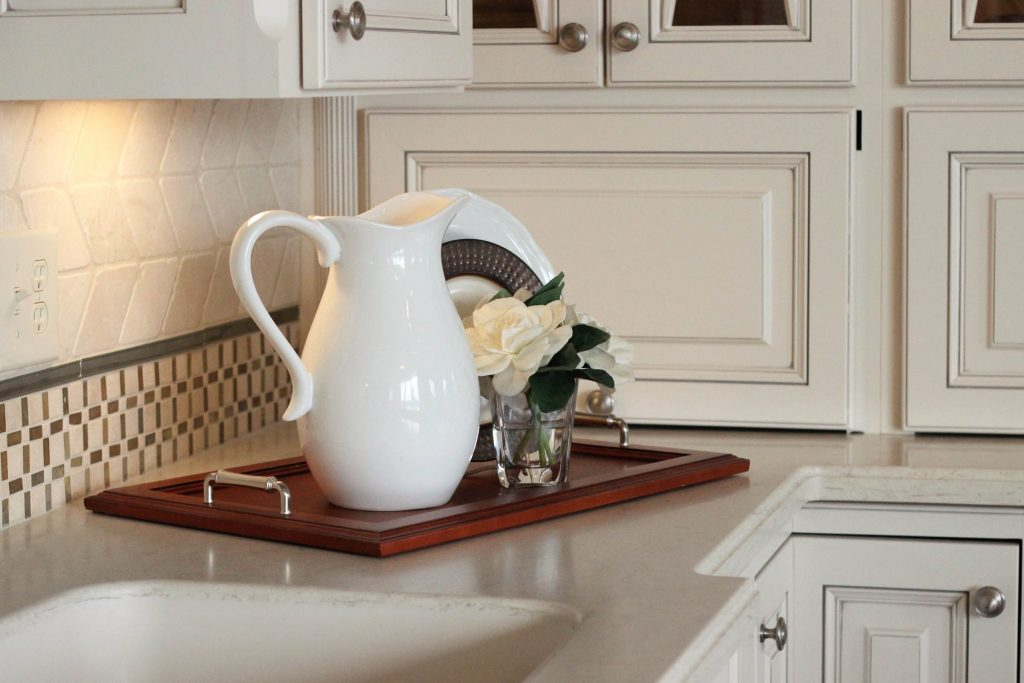 White pitcher on wooden tray sitting on new kitchen counter