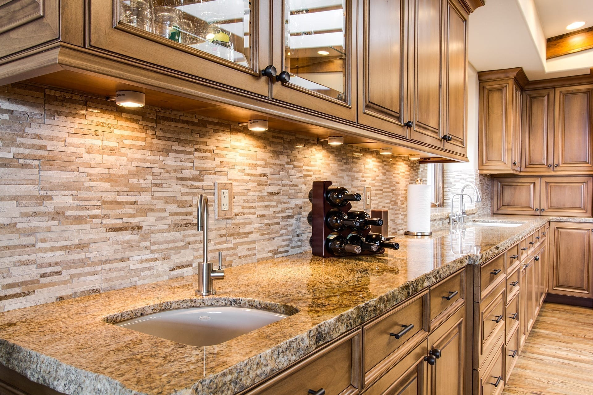 Brown granite countertop and wood cabinets with sink and wine