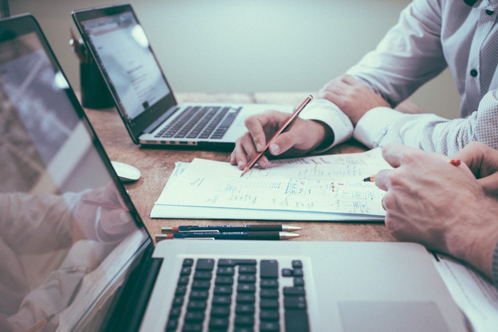 Laptop and men's hands reviewing bathroom renovation budget at desk